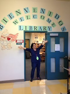 Ms. Sasamoto by welcome/bienvenidos library sign
